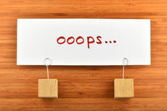 Oops en pappers- anmärkning med hållare som isoleras på träbakgrund Fotografering för Bildbyråer