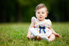 Oops!. Image of adorable baby girl sitting on grass making funny face, shallow depth of field stock photos