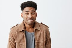 Oops. Portrait of unhappy young good-looking afro american men with curly hair in casual stylish clothes looking at. Oops. Portrait of unhappy young good-looking Stock Photography