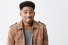 oops Stående av olyckliga unga snygga afro amerikanska män med lockigt hår i tillfällig stilfull kläder som ser arkivbild