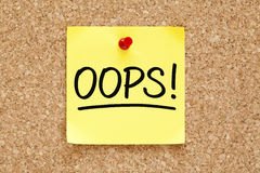 Oops Sticky Note. Oops! on yellow sticky note pinned with red push pin on cork board royalty free stock photography
