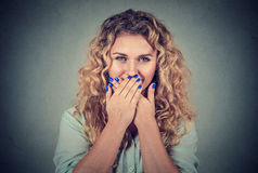 Oops! Surprised woman covering mouth with hands staring at camera Stock Images