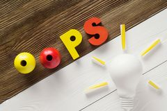 Oops word from colorful wooden letters on wooden table. Oops word from colorful wooden letters on two color wooden table, top view Royalty Free Stock Photography
