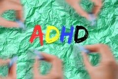 Oordning för hyperactivity för uppmärksamhetunderskott - ADHD-text med den färgrika bokstaven på grön bakgrund royaltyfri foto