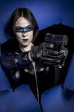 Oorlog, Brunette in zwart latexkostuum met pistool over gebroken pap royalty-vrije stock afbeeldingen