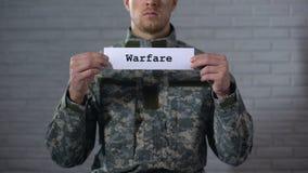 Oorlogvoeringswoord op teken in handen van mannelijke militair wordt geschreven, militair conflict dat stock footage