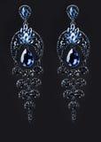 Oorring met kleurrijke blauwe gemmen op zwarte stock afbeeldingen