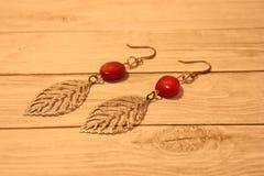 Oorringen met rood koraal op een lichte achtergrond Mooie juwelen voor vrouwen Handwork stock afbeeldingen