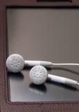 Oortelefoons bij de tabletbezinning Stock Afbeelding