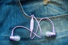 Oortelefoons in de zak jeans stock afbeelding