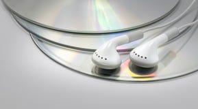 Oortelefoons op Compact-discs Stock Foto's