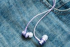 Oortelefoons op de oppervlakte van jeans royalty-vrije stock foto