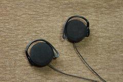 Oortelefoons tegen een oosters tapijt Royalty-vrije Stock Afbeeldingen