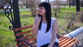 Oostelijk mooi meisje in een witte blousezitting in een park die op een bank, het glimlachen en begin op de telefoon, emoties spr stock video