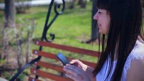 Oostelijk mooi meisje in een witte blousezitting in een park op een een smartphone houden en bank die, emoties lachen stock videobeelden