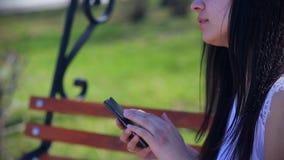 Oostelijk mooi meisje in een witte blousezitting in een park op een een smartphone houden en bank die, emoties lachen stock video