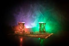 Oostelijke thee in traditionele glasse en pot op zwarte achtergrond met lichten en rook Oostelijk theeconcept Armudu traditionele stock fotografie
