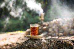 Oostelijke zwarte thee in glas op een oostelijk tapijt Oostelijk theeconcept Armudu traditionele kop De achtergrond van de zonson royalty-vrije stock afbeelding