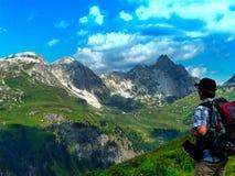 oostenrijk alpen Een wandelaar onderzoekt de afstand Een wandelaar met een rugzak bekijkt de rotsen royalty-vrije stock afbeeldingen
