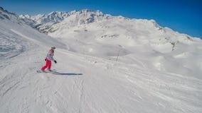 Oostenrijk - een meisje die onderaan de helling in Alpen snowboarding royalty-vrije stock fotografie