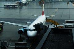 Oostenrijks die luchtvaartlijnenvliegtuig bij luchtbrug wordt gedokt Stock Foto