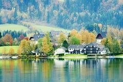 Oostenrijkse Plattelandshuisjes op meerbank Stock Foto's