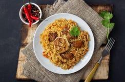 Oosterse Keuken Oezbekistaans pilau of plov van rijst en vlees in een gietijzerpan op houten rustieke raad royalty-vrije stock foto