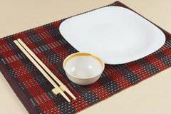 Oosterse schotels en eetstokjes op rode bamboemat royalty-vrije stock afbeelding