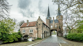 Oostpoort Delft NL in cloudy early morning. Grey clouds hover over the historical Eastport of Delft The Netherlands The wed cobblestones are always a thread Stock Image