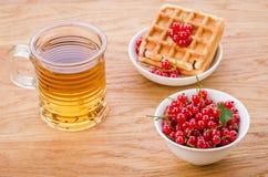 Opłatki z czerwonymi jagodami, szkłem i szkłem herbata herbata, opłatki z czerwonymi jagodami/ Selekcyjna ostrość zdjęcia royalty free