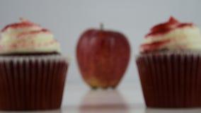 Opções saudáveis do alimento Os começos focalizaram em um queque vermelho, então transições a uma maçã vermelha filme