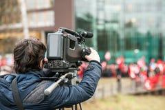 Opérateur d'appareil-photo travaillant dehors pendant l'événement vivant de dernières nouvelles image libre de droits