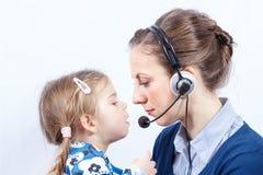 Opérateur de centre d'appels avec l'enfant photo stock