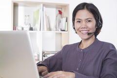 Opérateur de sourire heureux de support à la clientèle de femmes de l'Asie avec le casque photographie stock libre de droits