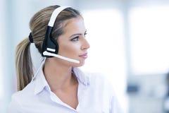 Opérateur féminin de sourire de service d'assistance avec des écouteurs photo stock