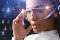 Opérateur féminin songeur employant la technologie de l'avenir Photo stock