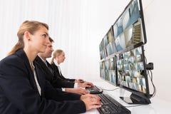 Opérateurs de système de sécurité regardant la longueur de télévision en circuit fermé Photo stock