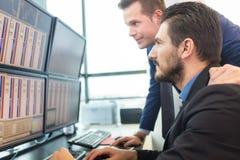 Opérateurs en bourse regardant des écrans d'ordinateur Photo stock