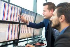 Opérateurs en bourse regardant des écrans d'ordinateur Image stock