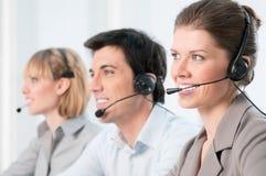 Opérateurs heureux de centre d'attention téléphonique Photos stock