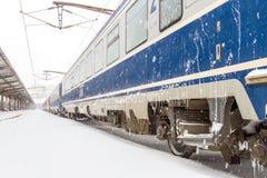 Opóźniający pociąg przy stacją podczas śnieżnej burzy Fotografia Stock