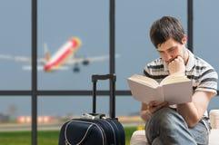 Opóźniający samolotu pojęcie Mężczyzna siedzi z bagażem w lotnisku fotografia stock