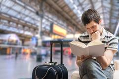 Opóźniający taborowy pojęcie Mężczyzna siedzi w dworcu i czytelniczej książce zdjęcie royalty free