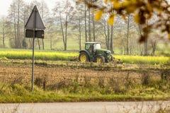 Opóźniona jesień Ciągnik orze pole blisko krawędzi las fotografia stock
