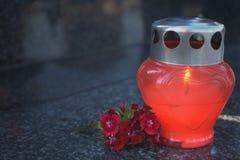 Opłakiwać świeczkę i czerwień kwitnie na nagrobku fotografia royalty free