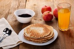 Opłatki, dżem, jabłka, soku pomarańczowego stojak na drewnianym stole obrazy royalty free