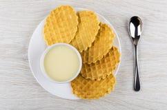 Opłatkowi ciastka, puchar z zgęszczonym mlekiem w bielu talerzu, teaspoon Zdjęcie Stock