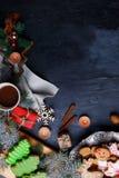 Op achtergrond is een schotel en een raad met peperkoeken, kop thee, verscheidene pijpjes kaneel en een takje van een boom Stock Fotografie