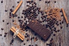 Opłatki w czekoladzie na drewnianym stole z kawowymi fasolami i kakaowym proszkiem na widok Zdjęcie Royalty Free