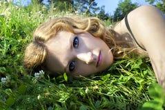 Op de aard van het mooie meisje in het gras Stock Afbeeldingen